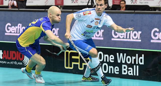 En svensk spelare försöker att nå bollen när en finsk anfallare springer förbi.