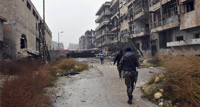 Militärer går på en väg. På sidan står hus som är skadade av krigets bomber.