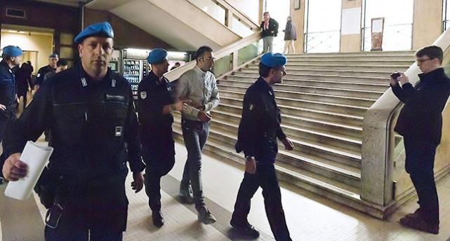En man med handbojor går omgiven av tre vakter.