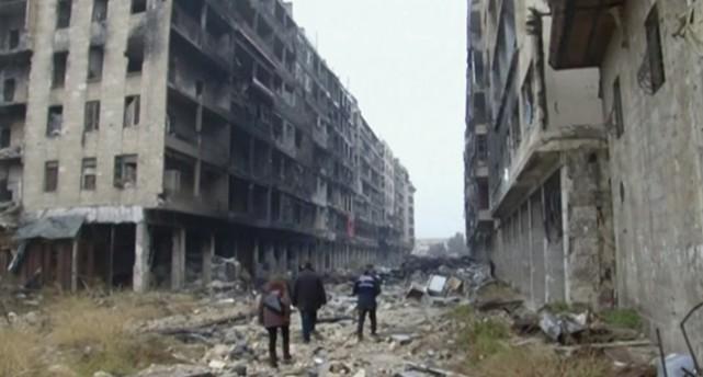 Människor på en gata med hus som är svårt skadade av bomber.