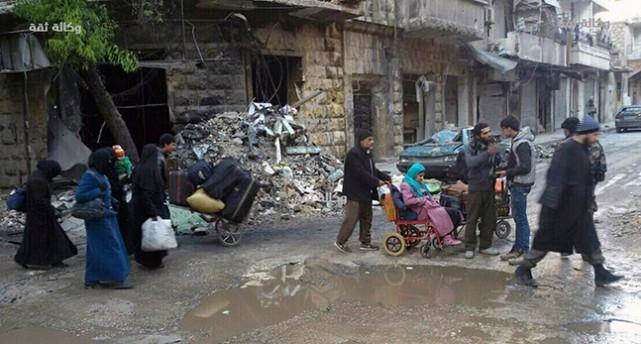Några personer lämnar den sönderbombade staden Aleppo.