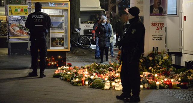 Poliser vaktar och bredvid finns många ljus och blommor.