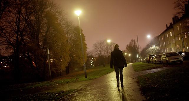 En person går en gångstoig en mörk kväll.