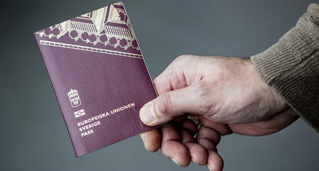 En hand håller ett svenskt pass.