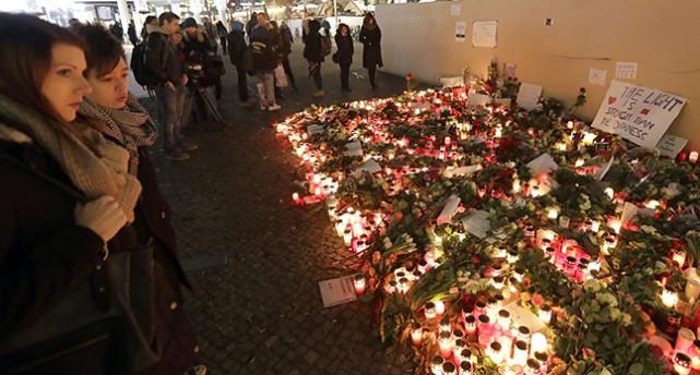 Människor står runt en plats med blommor och tända ljus.