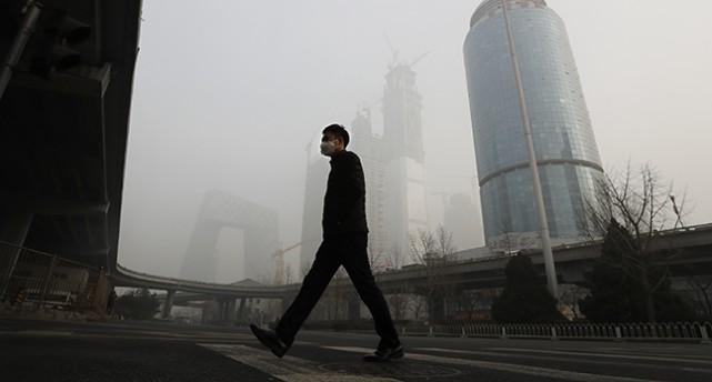 En man på en gata går med mask för munnen. I bakgrunden syns en grå dimma.