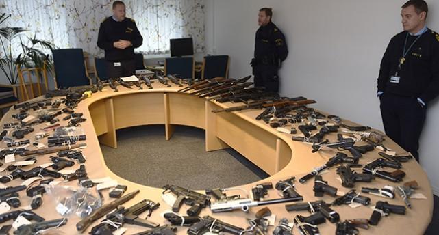 Ett ovalt bord med hål i mitten med massor av vapen på. Kring bordet står flera poliser.