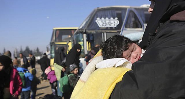 En kvinna bär ett barn vid bussarna som kört folk från Aleppo