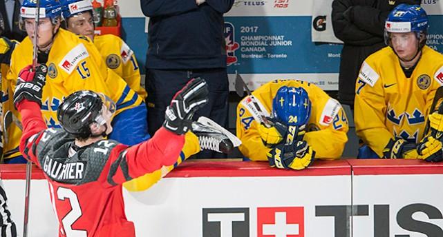 En kanadensisk spelare åker framför den svenska båset och jublar