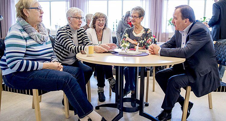 Statsminister Stefan Löfven vid ett bord med fyra äldre damer.