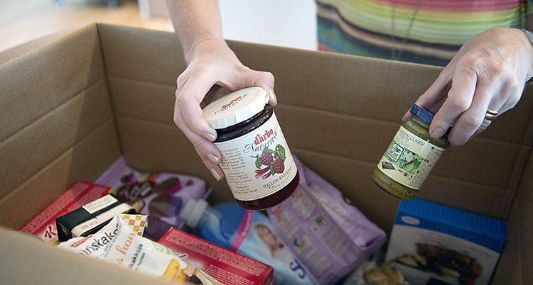 Händer sträcker sig efter mat i en låda.