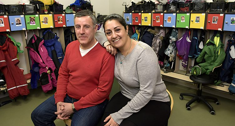 Två personer sitter i ett kapprum på ett dagis och ser glada ut