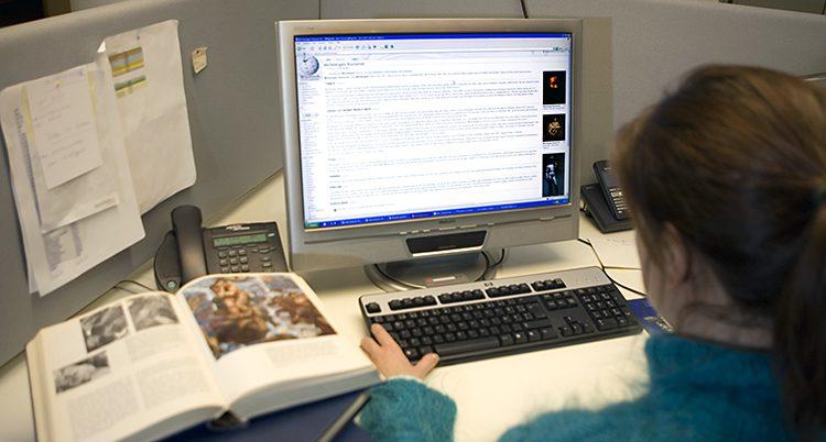 En kvinna sitter framför dator med sajten Wikipedia öppen.