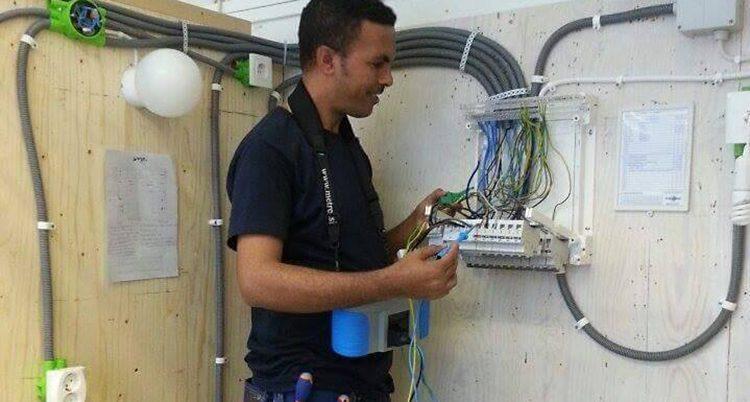 Mehari har arbetskläder och håller på med kablar