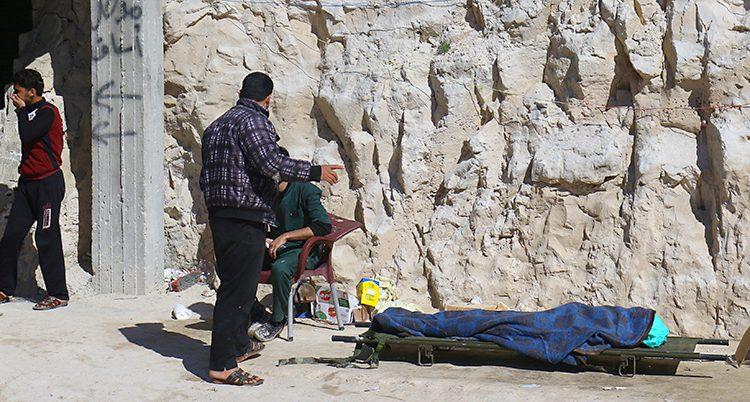 En person ligger under en filt på en bår.