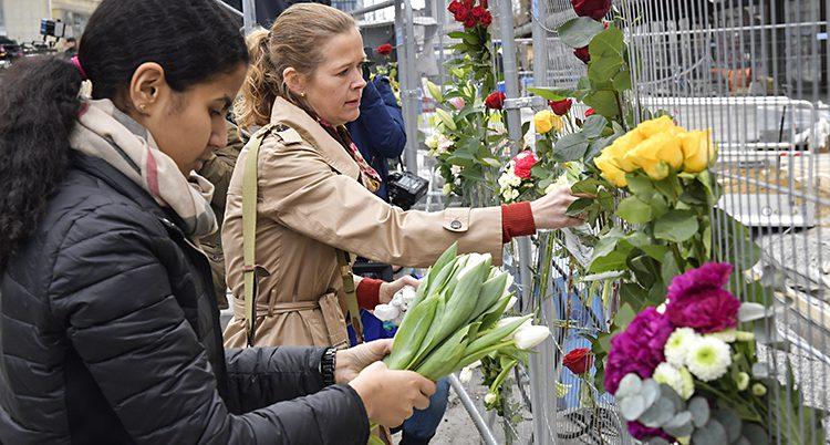 En kvinna hänger blommor på ett staket