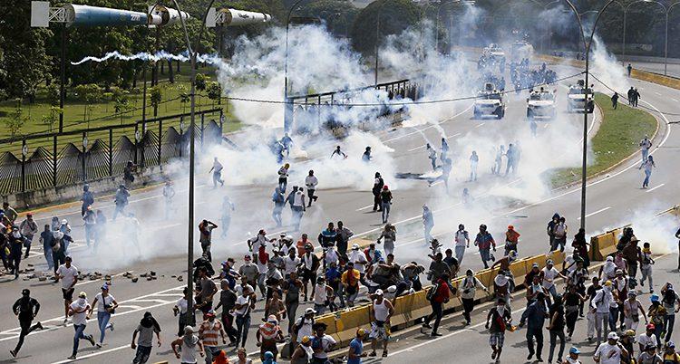 Poliser sprutar tårgas
