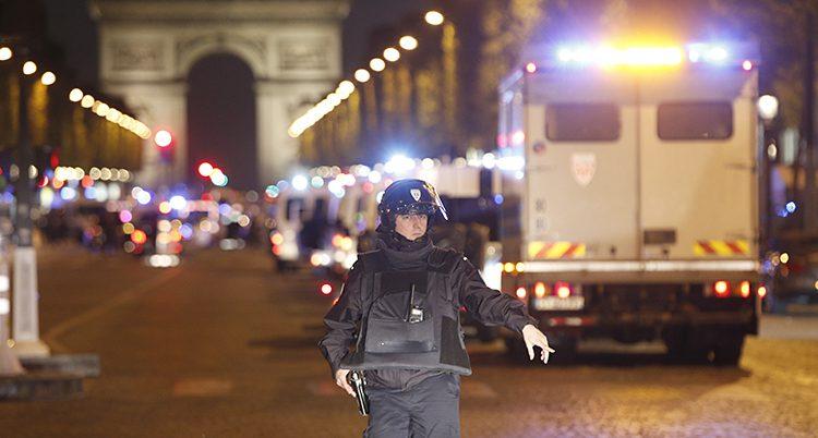 En polis framför triumfbågen i Paris