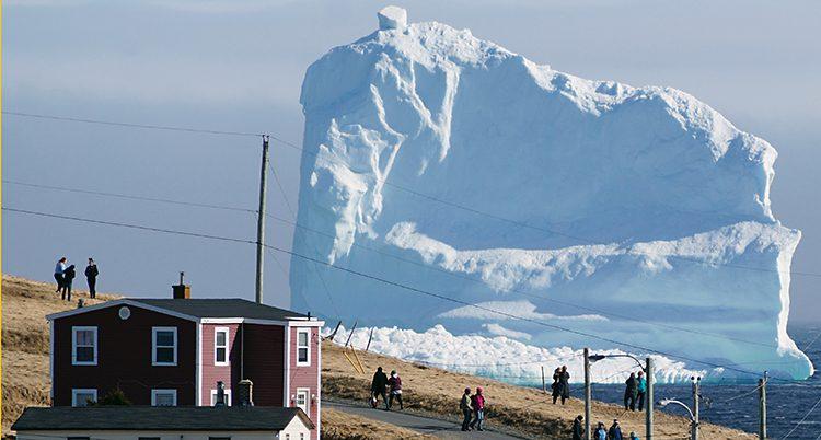 Ett stort isberg syns bakom ett litet rött hus