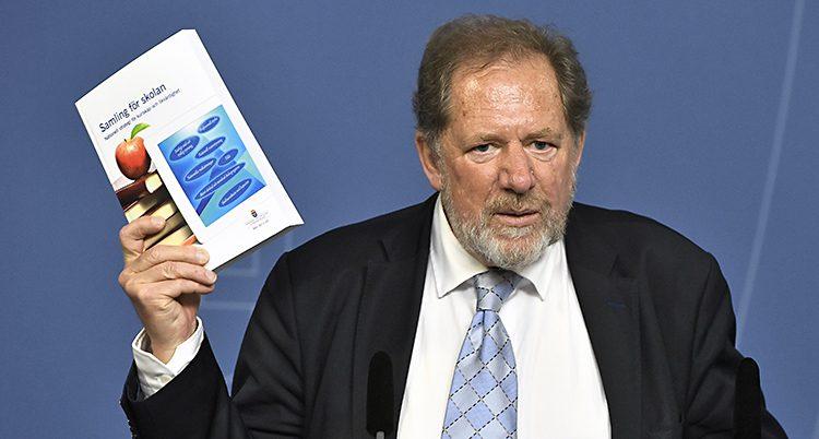 Jan-Eric Gustafsson från Skolkommissionen håller upp en bok med förslag