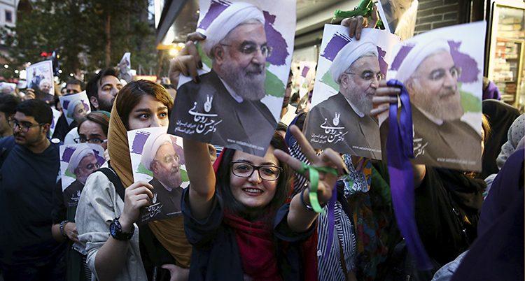 Människor håller upp skyltar med Irans president Rohani.