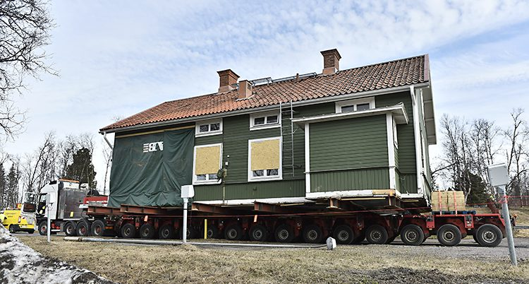 Ett stort grönt hus på ett flak till en lastbil