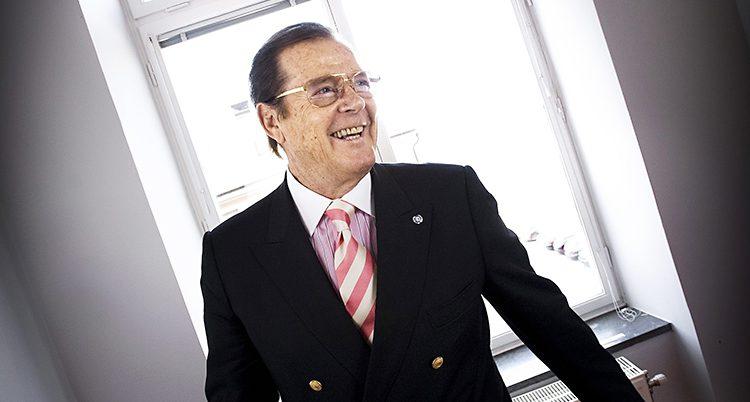 Roger Moore står framför ett fönster och ler