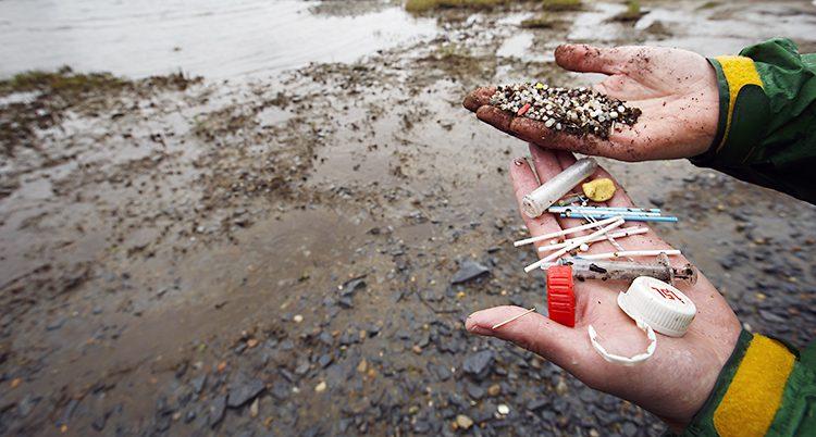 En hand visar skräp som hittats vid en strand.