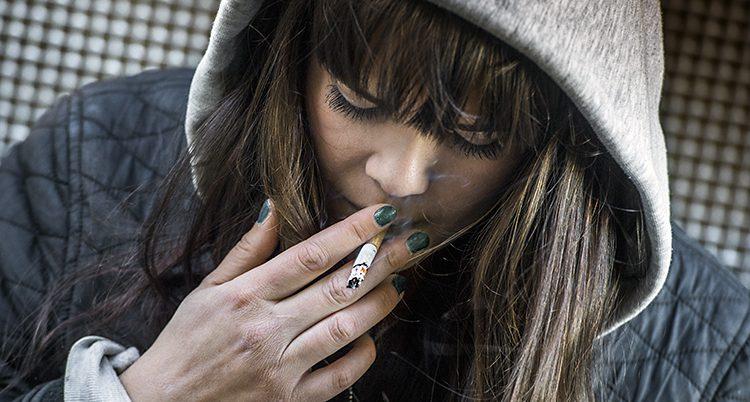 En ung tjej röker en cigarett