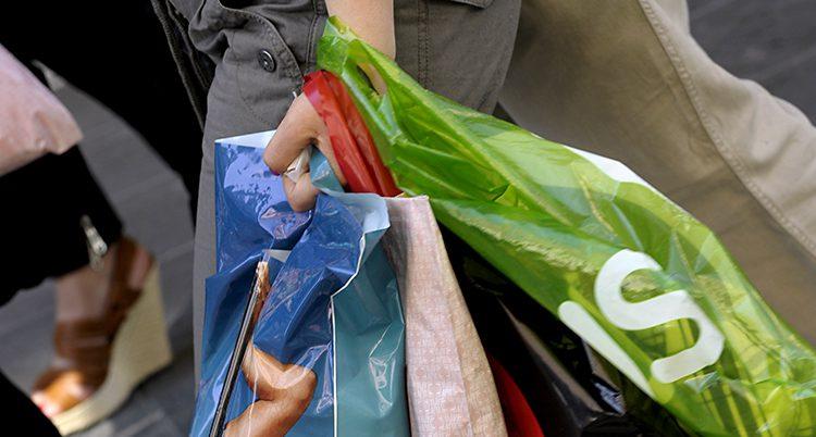 En kvinna med många plastpåsar