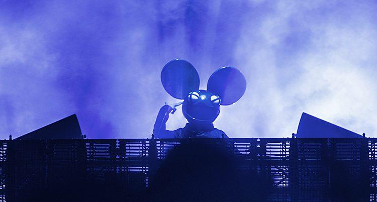 En bild på en person iklädd stora musliknande öron och motorcykelhjälm som spelar. Bilden är tagen underifrån och artisten syns som en svart silhuett mot ett blått starkt ljus.