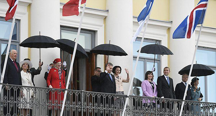 Flera kungligheter vinkar från en balkong på Finska presidentens slott.