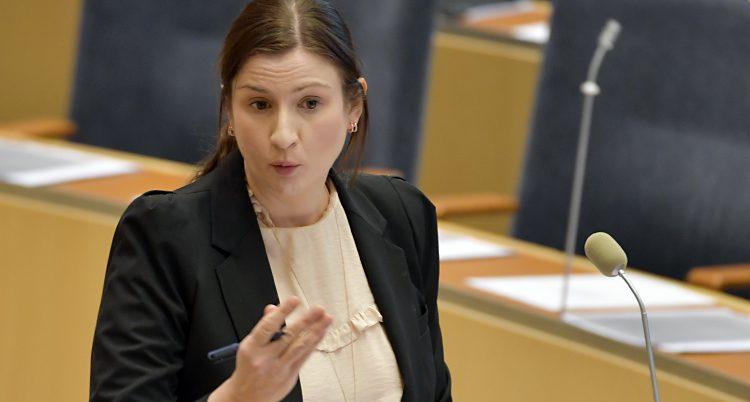 Birgitta Ohlsson debatterar i riksdagen. Hon har en beige blus med rysch och en svart kavaj.