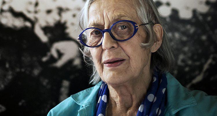 En ansiktsbild på Rosa Taikon. Hon bär glasögon med blå skalmar. En mörkt turkos skjorta och runt halsen en blå scarves med vita stora prickar.