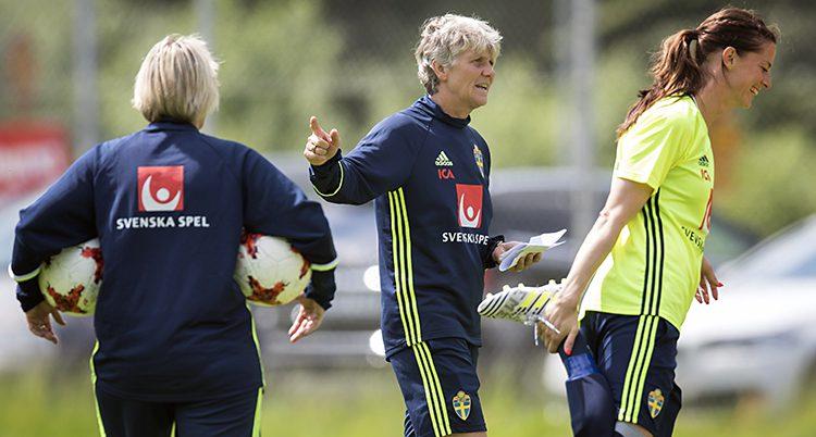Pia Sundhage och två spelare som värmer upp.