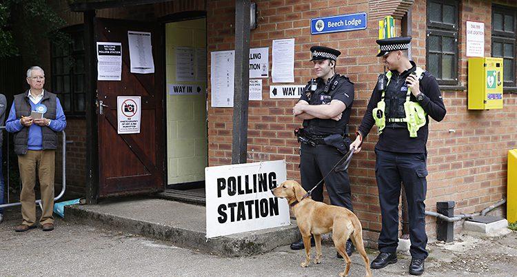 Poliser med en hund utanför ett tegelhus