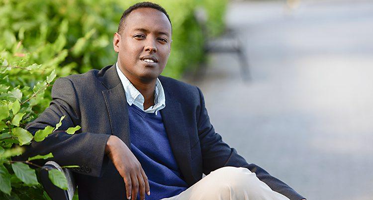 Ahmed Abdirahman sitter på en bänk utomhus.