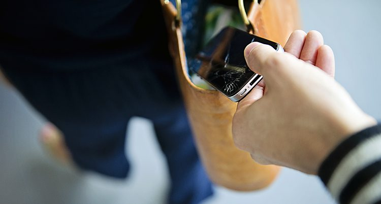 En hand tar en mobil ur en öppen väska