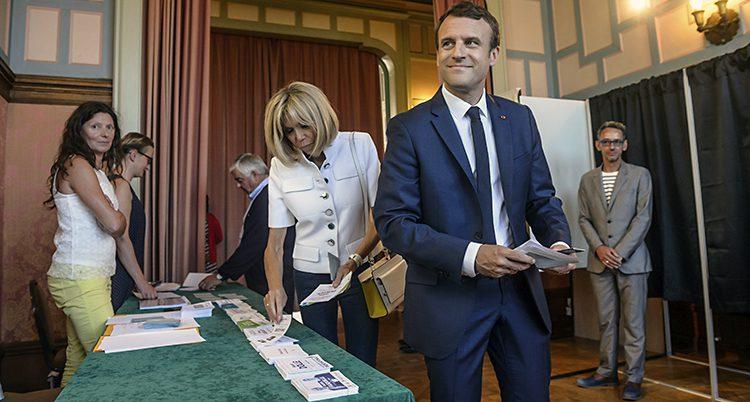 Emmanuel Macron ser glad ut i en vallokal