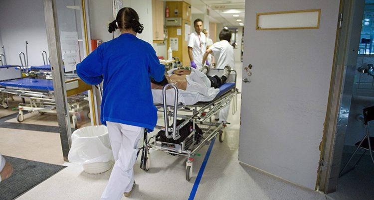En kvinna rullar en säng på ett sjukhus.
