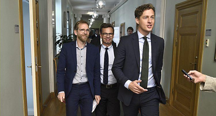 De tre politikerna går i en korridor.
