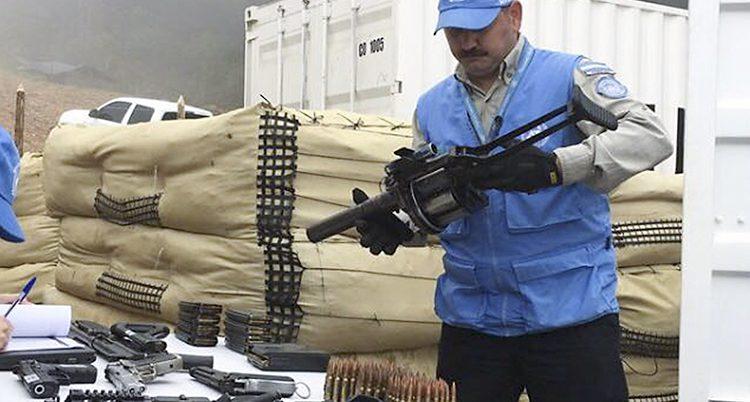 En man i blå väst undersöker ett vapen