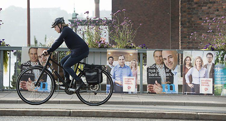 En cyklist cyklar förbi affischer om valet år 2014.