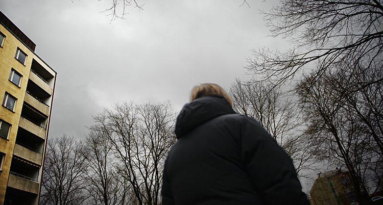 En ensam kvinna står utomhus med ryggen mot kameran.