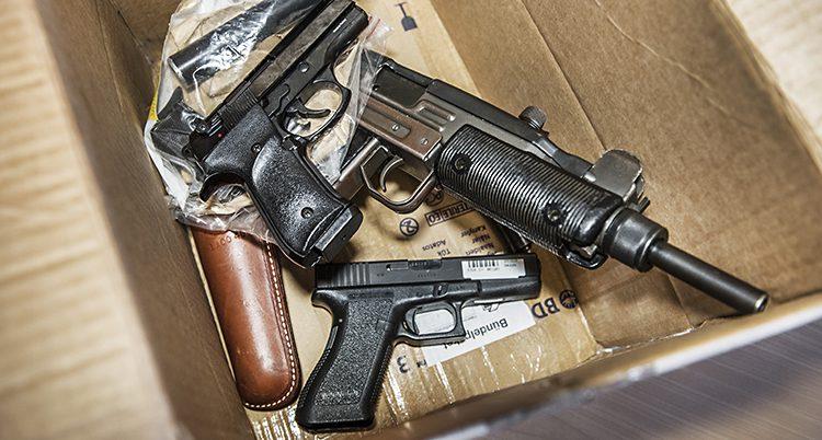 En kartong med flera pistoler i.