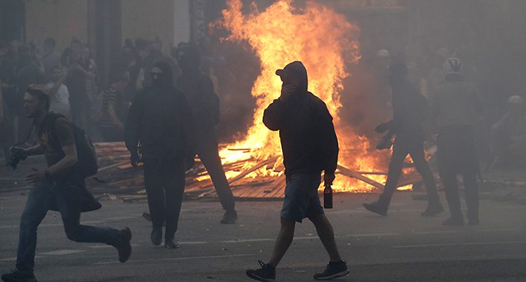 Svartklädda demonstranter går omkring på en gata i Hamburg. Bakom dem brinner en stor eld.
