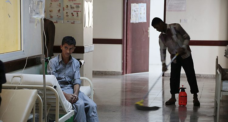 En pojke sitter med droppställning på en brits i en spartanskt inredd sjuksal. Snett bakom honom går en man med mopp och städar.