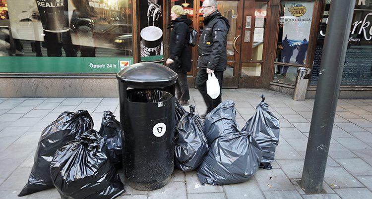 Sopor på en gata i Stockholm. Stora svarta sopsäckar ligger slängda bredvid en papperskorg.