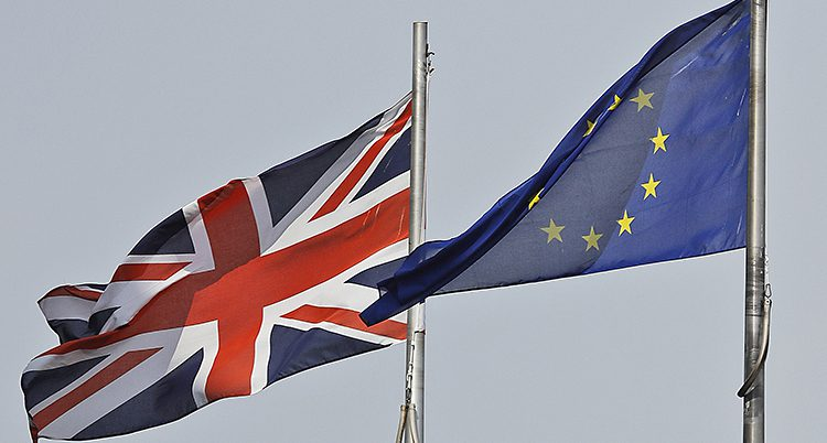Två flaggor på varsin stång blåser i vinden. Ena flaggan är Storbritanniens blå, vit, röda. Den andra flaggan är EUs med gula stjärnor i en ring på blå botten.
