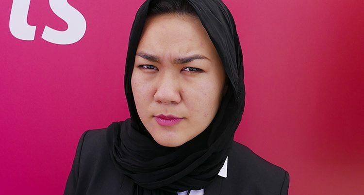 En ung kvinna med svart sjal över håret står mot en rosa bakgrund.